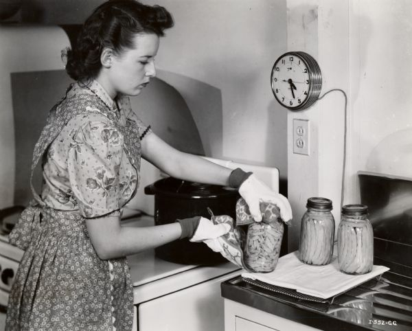 A woman removes a jar of cut string beans from a pot and places it on a dishcloth next to two other filled jars.