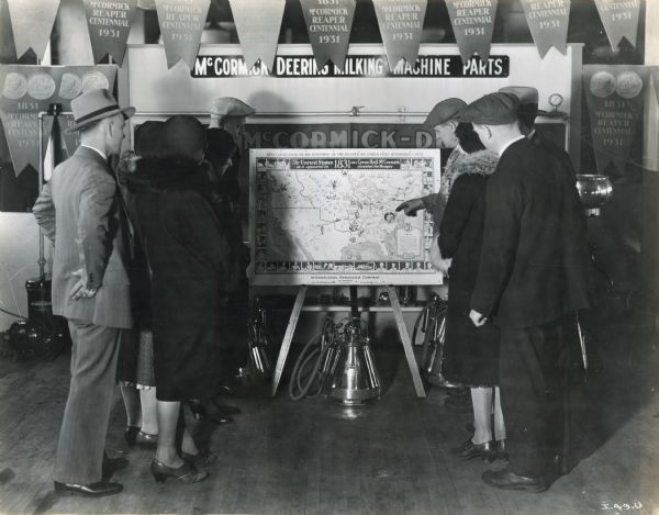 "A group of people look at an 1831 United States map, part of a McCormick-Deering milking machine parts display.  The title on the map reads, ""The United States as it appeared in 1831, the year Cyrus Hall McCormick invented the Reaper."" The map was produced for the Reaper Centennial celebration."