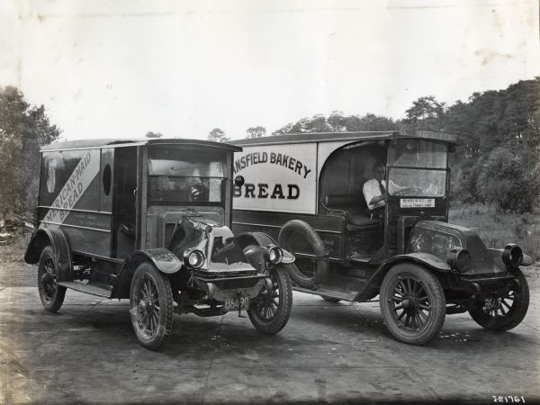 "Two bakery trucks reading ""American-Maid Bread,"" ""...ansfield Bakery,"" and ""New England Bakery Co."" are parked side by side in a paved lot."