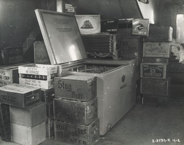 Wooden crates are piled around a McCormick-Deering 6-can milk cooler used for cooling beer at Mr. Jay Winter's tavern.