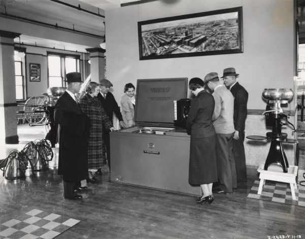 Three ladies and four men examine a McCormick-Deering 6-can milk cooler at a dealership or branch house. The photograph was taken in a large well-lit room with some other McCormick or milking related products.  A large photograph of McCormick Works hangs above the cooler, and a poster advertising a McCormick All-Steel Spreader hangs in the back.