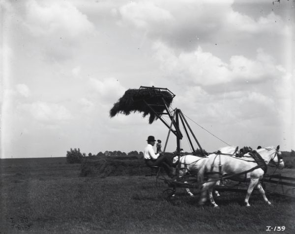 Man driving a hay stacker mounted on a jin-pole lifting hay in air behind. A boy wearing striped shirt and overalls on is standing on a haystack in the background. Other men wearing hats are behind the horses.