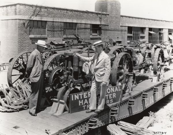"Two well-dressed men are standing outdoors among Farmall tractors which are loaded on railroad cars. Original caption reads: ""M.E. Merseran, manager, and H.W. Martin, assistant manager, Boston general line branch."""