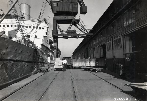 "Men loading large ""International Motor Truck"" crates onto a ship with a crane. Men are working near the ship, and people are watching from the second-story of the building on the right."