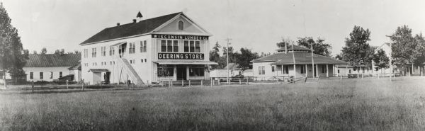 "An external view from a field of the Wisconsin Lumber Company's ""Deering Store."" A number of other buildings surround the store."