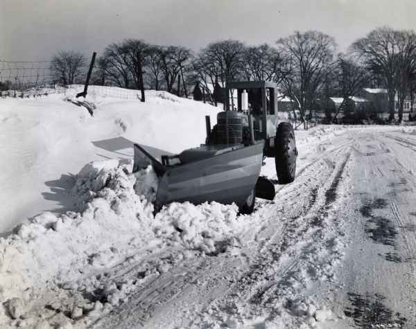 "Man plows snow with an International M tractor and snowplow. Original caption reads: ""Then equipped with Trojan Vee-type snow plow as shown, the Trojan one-man speed patrol, which is powered by International M tractor, becomes a very efficient dual-purpose snow remover. Its regular blade supplements the snow clearing action when in down position and can be used to bench the snow on side bank when raised. It is shown at work near Batavia, New York, where snowfall has been unusually severe this season.  The Trojan Vee-plow with its expanding curve moldboard has a cutting width of 72 inches. It is raised and lowered hydraulically. The maintainer blade is 10 feet long and has a swing of 90 degrees. It has a side shift (per side) of 15 inches, clearance of 12 inches, and penetration of 5 inches. The Trojan maintainer is a fast-moving outfit, its speeds varying from 2 to 16 miles per hour, and of course on its pneumatic tires it can travel on all sorts of roads."""