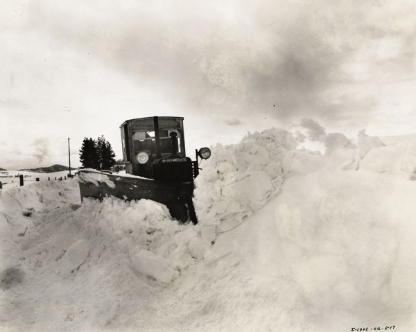 Man operating an International TD-35 crawler tractor (TracTracTor) and an Isaacson snowplow to clear a road in Kootenai County. According to the original caption, one to twenty miles were cleared per day, depending on the depth of the snow.
