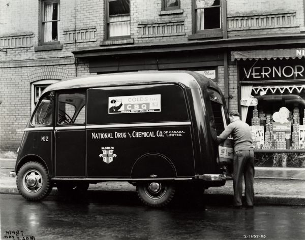 A man stands at the back of an International D-15-M (Metro) truck owned by the National Drug and Chemical Company of Toronto, Canada.  The side of the van has a sign for CBQ - a cold remedy.  A storefront with products and advertsing are in the background.