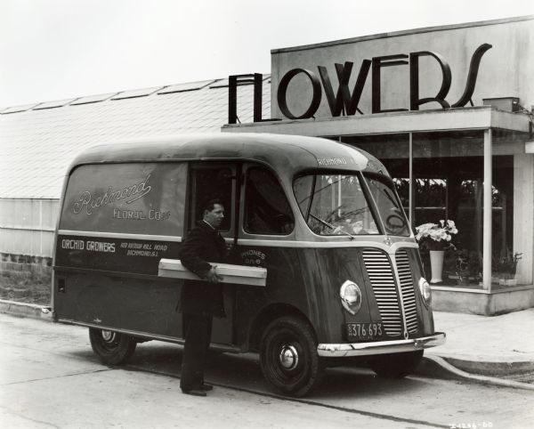 "International model D-2-M with 102 inch wheelbase and Metro body, owned by the Richmond Flower Company.  A man stands by the passenger side door with a long box under his arm.  The building behind has large letters that read ""FLOWERS"" over the entrance."