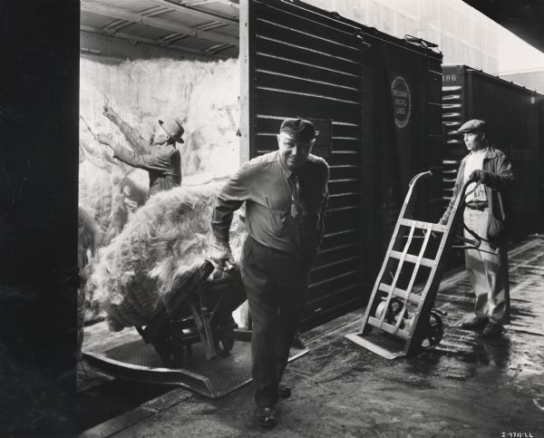 "Three factory workers unload bundles of sisal fiber (fibre) from a train at an International Harvester twine mill. A note with the companion photo to this image reads: ""Unloading fiber at an International Harvester twine mill from various parts of the world -- from Mexico, Cuba, Africa, Brazil, Haiti, the Philippine Islands, Central America, and elsewhere. This variety of sources provides fibers to produce the proper blends required to make baler and binder value to the IH quality standard."""