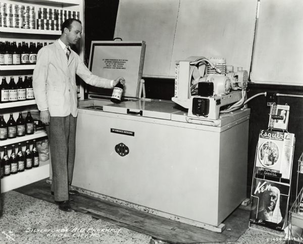 "A man stands by a cooler with a bottle of Pabst beer in his hand. Bottles and cans of beer are along the wall behind him. On the right is a magazine stand with the magazines <i>Coronet</i>, <i>Esquire</i>, and <i>Ken</i>. Original caption states: ""McCormick-Deering 4 in line beer cooler."""