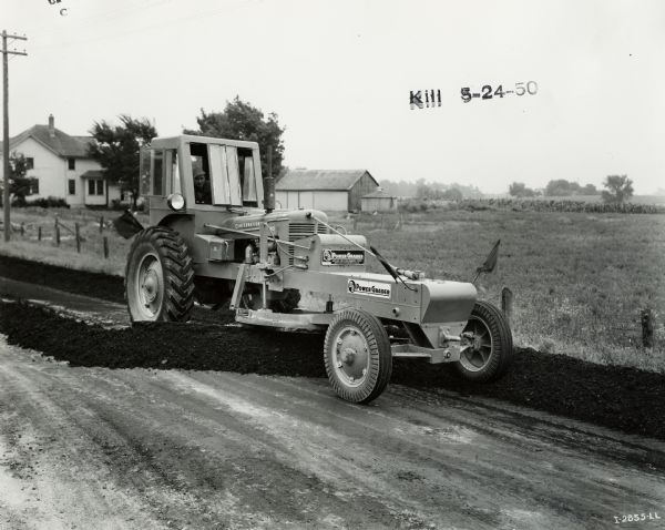 Man smoothing a road with a Meili-Blumberg (MB) Model 10 power grader attached to an International MD tractor. According to the original caption, the power grader had a 12-foot blade and was owned by Calumet County.