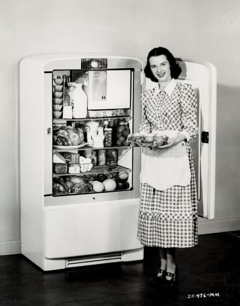 A woman in a checkered dress, apron, and heels stands in front of an open International Harvester refrigerator.  The door is behind her, and she holds a tray of food.  In the fridge is a variety of foods, including milk, jello cups, a dressed ham, fruits, vegetables, eggs, and canned items.