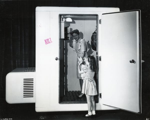 A girl hands a piece of poultry to a woman standing in an International walk-in cooler and freezer. They are standing in front of a curtain.