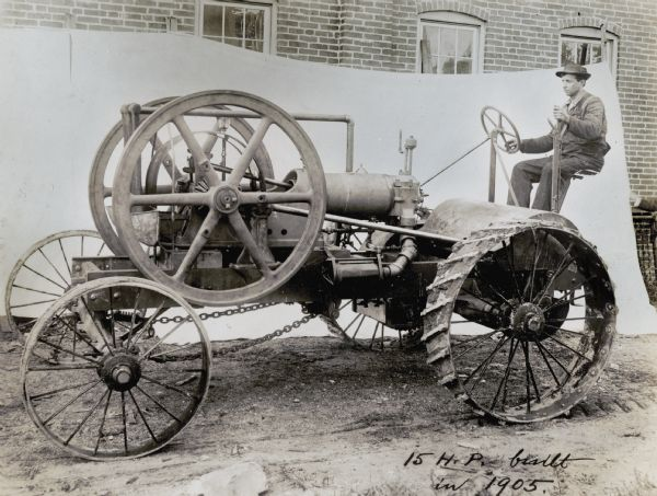 "A man sits behind the wheel of what appears to be an experimental tractor.  The location is staged for a photo shoot, with a white cloth hung in front of a brick building in the background. The handwritten text on the photograph reads, ""15 H.P. Built in 1905."""