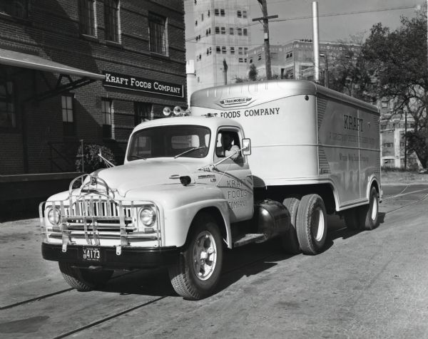 "A driver parks an International L-180 truck and Trailmobile trailer owned by the Kraft Foods Company along the side of a road in front of the company's plant. The original caption reads, ""The new L-180 International shown at the Kraft Foods Company's plant in San Antonio is one of ten motor trucks operated by the company in San Antonio, eight of which are Internationals. The trailmobile trailer is insulated and 18 feet long. It has double doors at the rear and also a door at one side. It is used to make store to store deliveries and averages 40 stops a day. The wheelbase of the truck is 142 inches. The truck is painted a very attractive attention-getting light yellow and white-shaded blue lettering."""