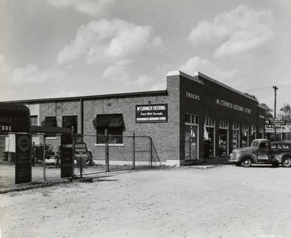 "Exterior view of the storefront of an International Harvester dealership with a truck parked in front. On the left is a chain-link fence, with a sign in the shape of a man pointing that says: ""LOOK / USED TRUCKS AND TRACTORS."""