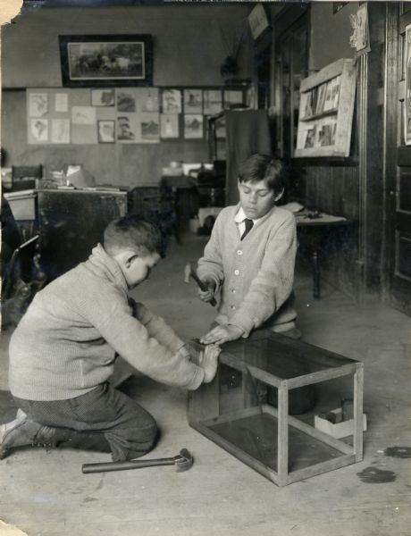 Two boys construct a fly trap. A boy holds mesh in place against a wooden box frame while another boy uses a hammer to nail it into place. They kneel in what appears to be an office or schoolroom, with furniture, and various objects are hanging on the walls in the background.