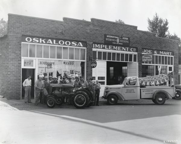 Exterior view of the Oskaloosa Implement Company, an International Harvester dealership. A group of men and young boys pose near a Farmall A Tractor, and on the right is an International D-2 truck.