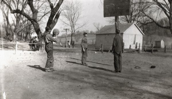 Three young men playing basketball on an outdoor court. In the background behind a fence and tree are a group of girls, and in the center background younger girls are playing on playground equipment near a building, possibly a school.