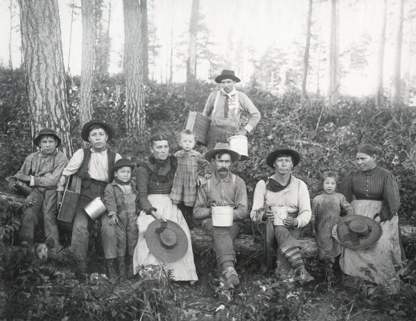 "Men, women and children holding boxes and pails in the forest. Original caption reads: ""VI Drive to W.S.; Chippewa blueberry pickers."" The photograph is part of an album devoted to ""Island Lake Camp"", a favorite vacation destination of Nettie Fowler McCormick; Cyrus McCormick, Jr.; Harold McCormick; Anita McCormick Blaine and other family members. The camp may have been located in Barron County, between Rice Lake and Ladysmith."