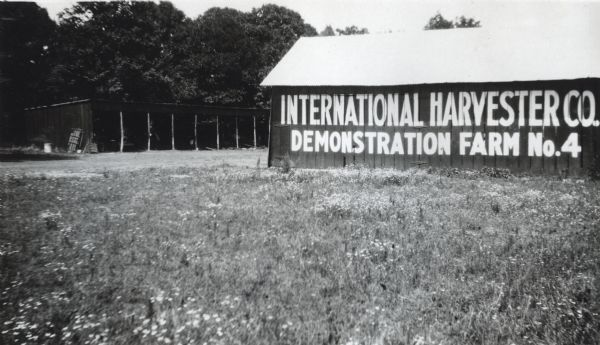 "View of the side of a milk house with a sign painted on it which reads, ""International Harvester Co. Demonstration Farm No.4."""