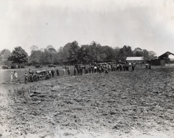 View across field on an International Harvester Company farm of group of men standing and watching a plowing demonstration. Several barns and other farm structures stand in the background.