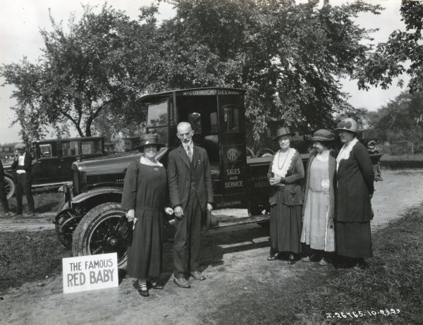 A group of women, and one man, are standing beside a McCormick-Deering Red Baby Speed Truck. The truck had a 1,500 pound capacity and was also known as the Model S. Other individuals are standing near another automobile in the background.