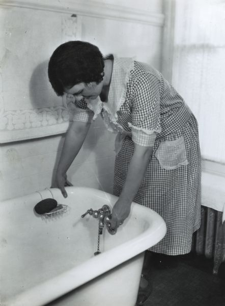 A woman wearing a checkered dress is turning the faucet on a bathtub at International Harvester's Hinsdale experimental farm (Harvester Farm).