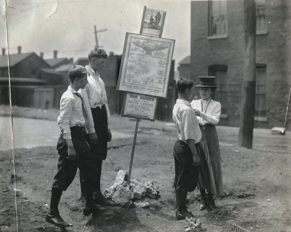 "Three boys and a woman standing near several signs advertising a war garden. The signs read (from top to bottom), ""Every Boy Can Feed a Soldier,"" ""Registered War Garden Under Protection of State Council Defense. Feed Yourself. A War Garden Will Do It. Be a Soldier of the Soil. Exempt No Land,"" ""To destroy the food supply is to give comfort to the enemy. Food Will Win the War,"" and ""War Garden. Protected and Registered. No Loyal American Will Steal or Destroy This Crop."""