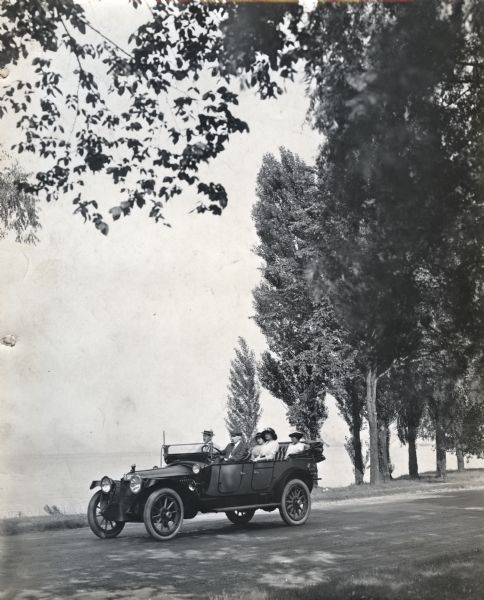 A group of two men and three women are riding on a rural dirt road in an automobile with its top folded down. There is a lake or river in the background.