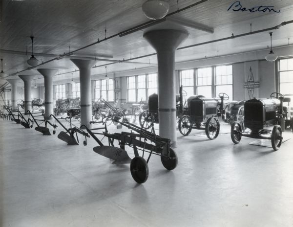 "McCormick-Deering tractors, plows, and other agricultural implements are arranged on display in a showroom. A sign advertising cream separators hangs on the wall, reading ""McCormick-Deering Primrose Separators. Good equipment makes a good farmer better."""
