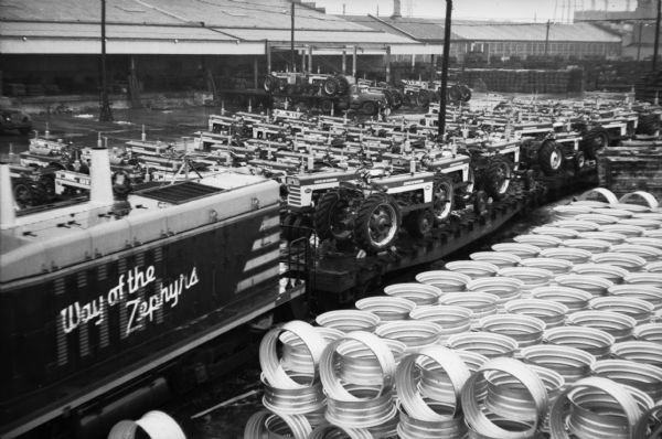 "Elevated view of Farmall tractors are loaded onto railroad cars as they prepare to leave International Harvester's Farmall Works factory. On the locomotive is painted a sign that reads: ""Way of the Zephyrs"". In the foreground are stacks of what appears to be tire rims."