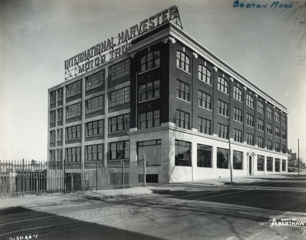 "Exterior view of an International Harvester Company branch building. Large show windows line the first floor along the sidewalk. A large electric sign on the roof reads, ""International Harvester Motor Trucks"" and street railroad tracks run down the street. Residential houses are in the far background."