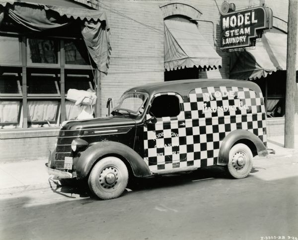 "An International Model D-2 truck owned by Model Laundry Company parked outside the business' storefront. The truck is painted in a checkerboard pattern and the text on its side reads, ""Model - Tone Cleaning. State License 27. Model Laundry Co."""