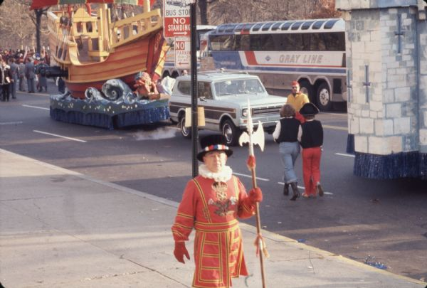 "Color photo of a Thanksgiving Day Parade, either Macy's Parade in Manhattan, New York, or Gimbels' Parade in Philadelphia, Pennsylvania. A man in the foreground walking along the sidewalk is in a red Beefeater costume with yellow and black pinstriping carries a polearm. He has a coat of arms consisting of a crown above three flowers on his chest, red gloves, and a black hat with a band made of red, white, and blue squares. Behind him is a ""Bus Stop, No Standing"" and ""No Parking"" sign. A pirate ship float towed by a blue and brown International Harvester Scout 4 x 4 is coming along the street, and a bus with the words ""Gray Line"" on the side is in the opposite lane. Spectators can be seen in the background."
