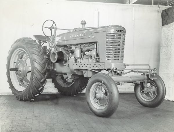 Three-quarter view from right front of a Farmall M tractor with adjustable wide front axle attachment.