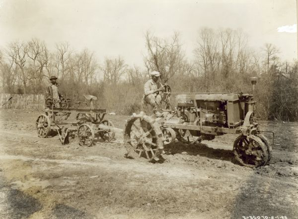 "Right side view of two men in a wet, muddy field. One of the men is driving a Farmall tractor which is pulling another man who is standing on the back of a Russell ""Junior."" Oscar E. Wood."