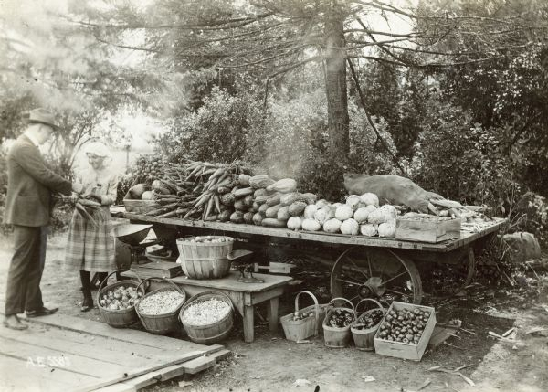 "Girl selling vegetables to a customer at vegetable stand along Milwaukee pike. Original caption reads: ""The little girl in charge sold over $800 worth of vegetables during the season."" Specific location unknown."