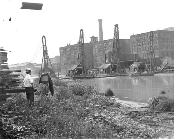 "Rear view of company photographer setting up shot of IHC's McCormick Works docks from across the waterfront. Two men are in a long wooden boat, with the name: ""Geo. H. Jackson"" on it along with ""Great Lakes Dredgers."" Four rafts, floating in the water and attached to each other with ropes, each have a small building on them with signs that read: ""River No. 5. Great Lakes Dredge & Dock Co."" Factory buildings and a smokestack are in the background."