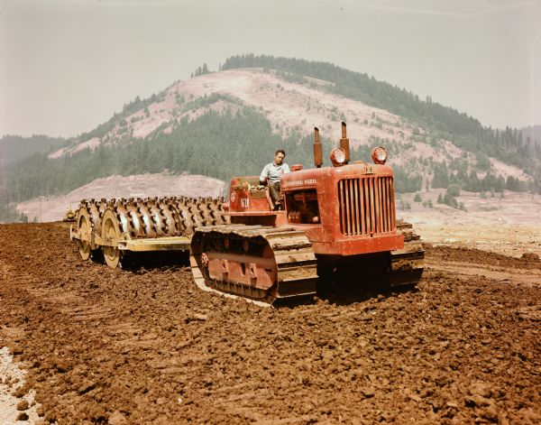 Color photograph of an International Diesel TD-24 crawler tractor with a sheepsfoot roller used for road construction on the south side of Dorena Lake Dam.