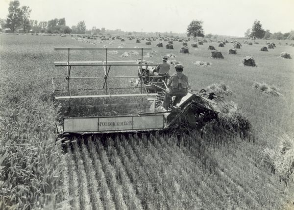 Elevated rear view of two men in a field operating a new McCormick-Deering F-20 tractor and M-4 power binder, which was owned and operated by Grover Evans, R.R. 2, Kirklin, Indiana. Farm buildings are in the distance on the left.