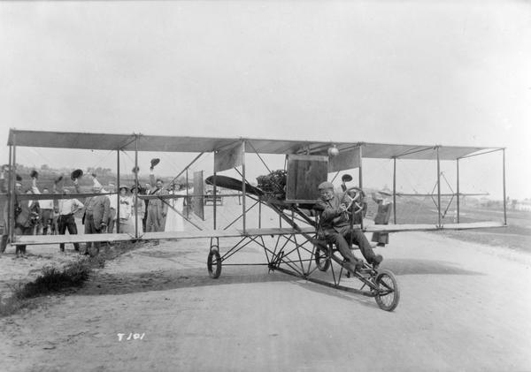 To the accompaniment of a cheering crowd, a pilot in a Curtiss pusher prepares to take off.