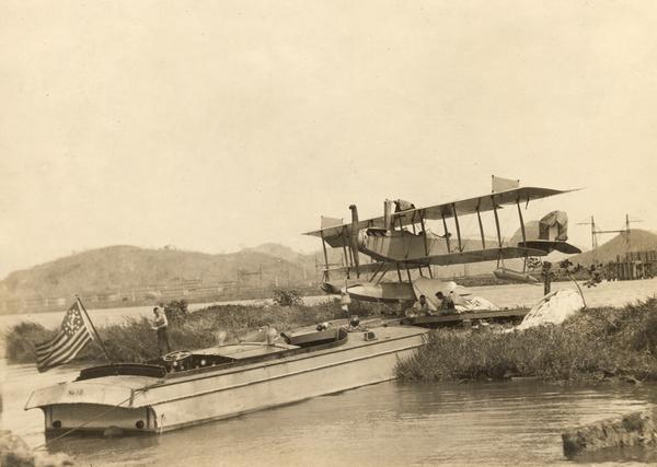 A Curtiss hydroaeroplane tied down prior to a test flight over San Diego Bay.  Two unidentified pilots rest on the dock in the shade of its wing.