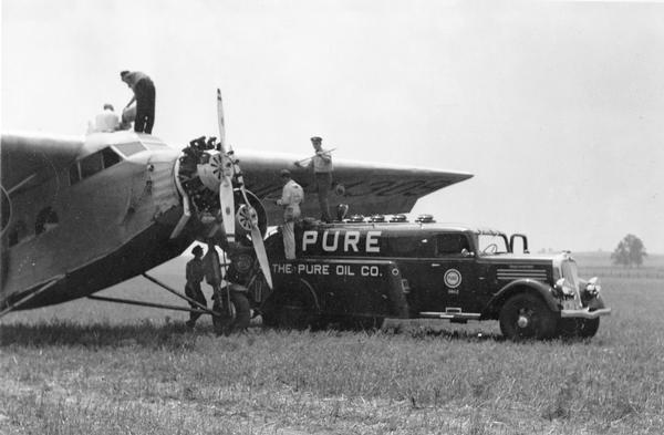 Refueling a Ford Tri-Motor airplane. Because gasoline truck hoses did not have pumps, airplanes were refueled by filling 5-gallon cans and then lifting the cans up to the fuel tank. The fuel was then siphoned through a chamois cloth to remove impurities.