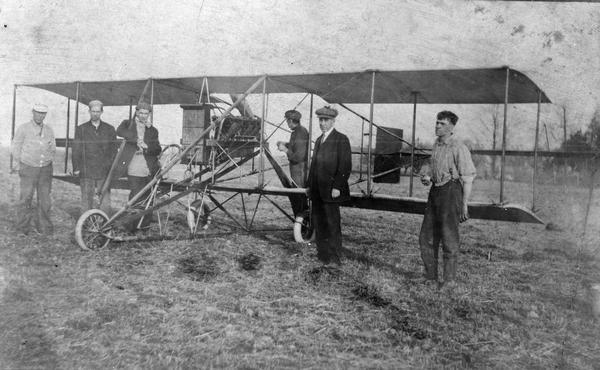 "John Kaminski (the first licensed pilot in Wisconsin, third from the right in checkered cap) with his new Curtiss pusher, the ""Sweetheart."""