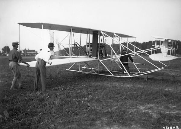 Wilbur Wright, in the bowler hat, preparing the Flyer for the conclusion of the test required to win a U.S. Army contract. The 1908 demonstration had been interrupted by a crash in which Orville was seriously injured and his passenger killed. This photograph shows clearly the track from which the early Flyers were catapulted and Wilbur's intense concentration.
