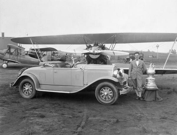 "John P. Wood of Wausau, winner of the 1928 National Air Reliability Tour, with his ""Waco from Wausau."" Also in the photograph are Wood's prizes: the Edsel B. Ford Trophy and a new Chrysler automobile."