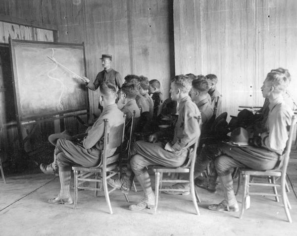 A visiting French officer instructs novice American pilots at Camp Mineola on the conditions that they can expect to find at the front.