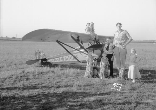 A group of circus performers pose outdoors with a Corben airplane. The tall Man is Jack Earle, and one of the little people is probably Lia Graf.